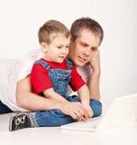 Padre e hijo con la computadora portátil Imagenes de archivo