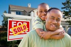 Padre e hijo con la muestra y el hogar de las propiedades inmobiliarias Imágenes de archivo libres de regalías