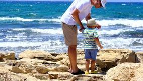 Padre e hijo con la parte posterior en el clifftop que mira la agua de mar azul hermosa metrajes