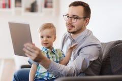Padre e hijo con la PC de la tableta que juega en casa Imágenes de archivo libres de regalías