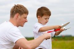 Padre e hijo con los aviones del juguete en parque Fotos de archivo