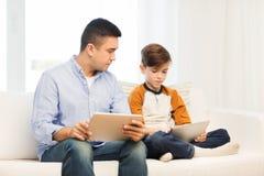 Padre e hijo con PC de la tableta en casa Fotos de archivo