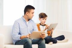 Padre e hijo con PC de la tableta en casa Imágenes de archivo libres de regalías