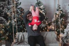Padre e hijo de 1 año que engañan alrededor delante del árbol de navidad que se sienta en el oscilación de madera en estudio Niño Fotos de archivo libres de regalías