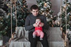 Padre e hijo de 1 año que juegan delante del árbol de navidad que se sienta en el oscilación de madera en estudio Fotografía de archivo