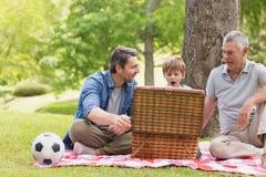 Padre e hijo de abuelo con la cesta de la comida campestre Imagenes de archivo