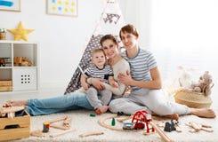 Padre e hijo de la madre de la familia que juegan junto en el ` s pl de los niños imagen de archivo
