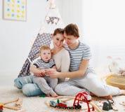 Padre e hijo de la madre de la familia que juegan junto en el ` s pl de los niños foto de archivo