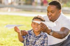 Padre e hijo de la raza mezclada que juegan los aeroplanos de papel imagenes de archivo