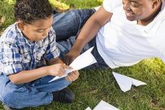 Padre e hijo de la raza mezclada que juegan los aeroplanos de papel fotografía de archivo libre de regalías