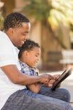 Padre e hijo de la raza mezclada que usa el ordenador de la pista de tacto Foto de archivo