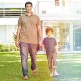 Padre e hijo en el jardín de la casa Foto de archivo libre de regalías