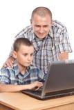 Padre e hijo en el ordenador Imágenes de archivo libres de regalías