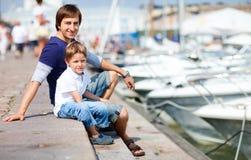 Padre e hijo en el puerto deportivo en centro de ciudad Fotografía de archivo