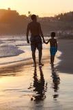 Padre e hijo en la playa en la puesta del sol Fotos de archivo