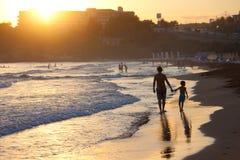 Padre e hijo en la playa en la puesta del sol Imagen de archivo libre de regalías