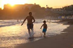 Padre e hijo en la playa en la puesta del sol Fotografía de archivo libre de regalías