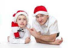 Padre e hijo en los sombreros de Papá Noel imagen de archivo libre de regalías