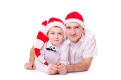 Padre e hijo en los sombreros de Papá Noel fotos de archivo