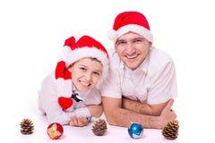 Padre e hijo en los sombreros de Papá Noel fotografía de archivo