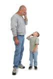 Padre e hijo en los teléfonos celulares fotografía de archivo
