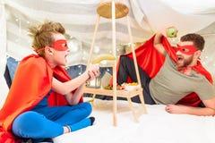 Padre e hijo en los trajes del super héroe que se divierten con las frutas en el fuerte combinado Foto de archivo