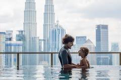 Padre e hijo en piscina al aire libre con la opinión de la ciudad en cielo azul fotos de archivo