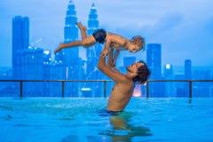 Padre e hijo en piscina al aire libre con la opinión de la ciudad en cielo azul imágenes de archivo libres de regalías