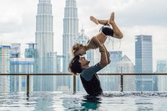 Padre e hijo en piscina al aire libre con la opinión de la ciudad en cielo azul foto de archivo