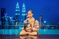 Padre e hijo en piscina al aire libre con la opinión de la ciudad en s azul fotos de archivo libres de regalías