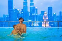 Padre e hijo en piscina al aire libre con la opinión de la ciudad en s azul fotografía de archivo