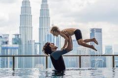 Padre e hijo en piscina al aire libre con la opinión de la ciudad en s azul imagen de archivo