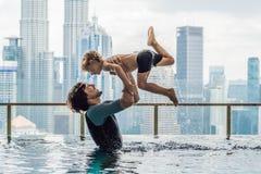 Padre e hijo en piscina al aire libre con la opinión de la ciudad en s azul imagen de archivo libre de regalías