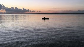Padre e hijo en un bote de remos Siluetas del canotaje de dos personas en la puesta del sol almacen de metraje de vídeo