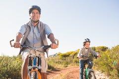Padre e hijo en un paseo de la bici Imagenes de archivo