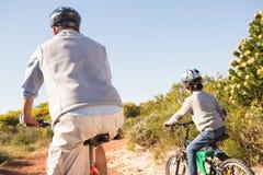 Padre e hijo en un paseo de la bici Fotos de archivo libres de regalías