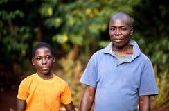 Padre e hijo en un pueblo en Uganda fotos de archivo