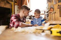 Padre e hijo felices con el modelo en el taller imagen de archivo