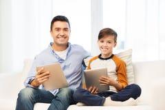 Padre e hijo felices con PC de la tableta en casa Foto de archivo