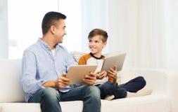 Padre e hijo felices con PC de la tableta en casa Imagen de archivo