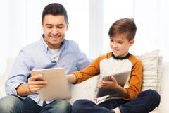Padre e hijo felices con PC de la tableta en casa Imágenes de archivo libres de regalías