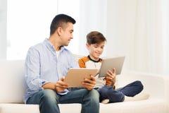 Padre e hijo felices con PC de la tableta en casa Fotos de archivo libres de regalías