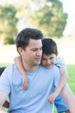 Padre e hijo felices del retrato en parque al aire libre imagen de archivo