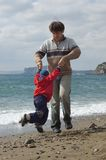 Padre e hijo felices en la playa Imagen de archivo libre de regalías