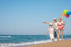 Padre e hijo e hija que juegan en la playa en el tiempo del día Imagenes de archivo