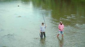 Padre e hijo ishing Caña para mosca y carrete con una trucha marrón de una corriente Padre feliz e hijo junto que pescan adentro metrajes