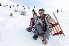 Padre e hijo jovenes en nieve con el trineo Imágenes de archivo libres de regalías