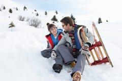 Padre e hijo jovenes en nieve con el trineo Foto de archivo