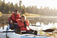 Padre e hijo kayaking en el lago rural, cierre para arriba Imagen de archivo