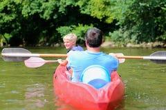 Padre e hijo kayaking en el río Foto de archivo libre de regalías